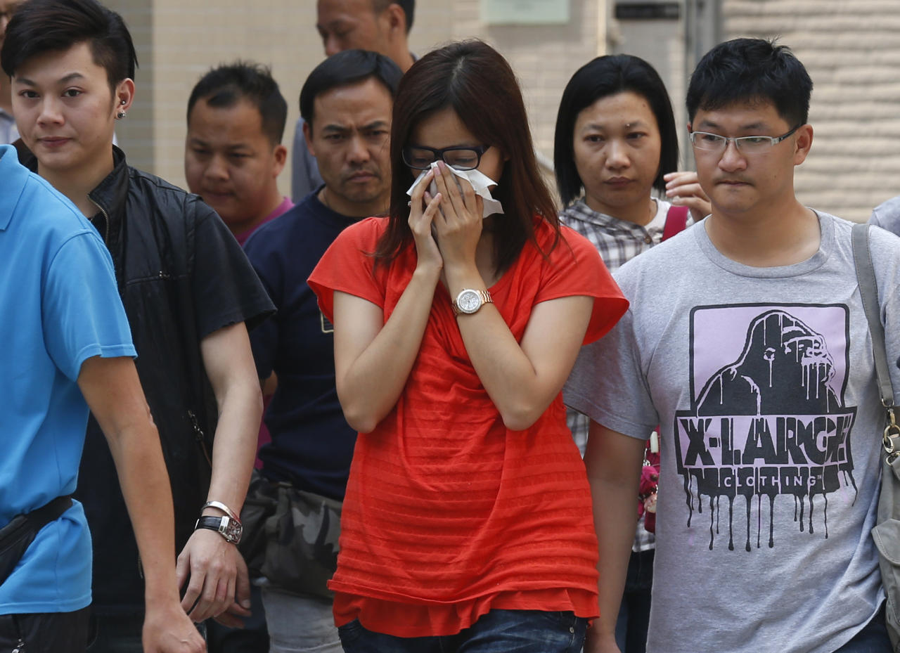 A woman, center, who lost her mother in a ferry collision, leaves a public mortuary with relatives of other victims, in Hong Kong Tuesday, Oct. 2, 2012. A ferry on Monday collided with a boat owned by utility company Power Assets Holdings Ltd., which was taking its workers and their families to famed Victoria Harbor to watch a fireworks display in celebration of China's National Day and mid-autumn festival, killing at least 36 people. (AP Photo/Kin Cheung)