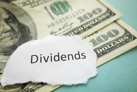 """Piece of paper that says """"dividends"""" sitting on top of $100 bills."""