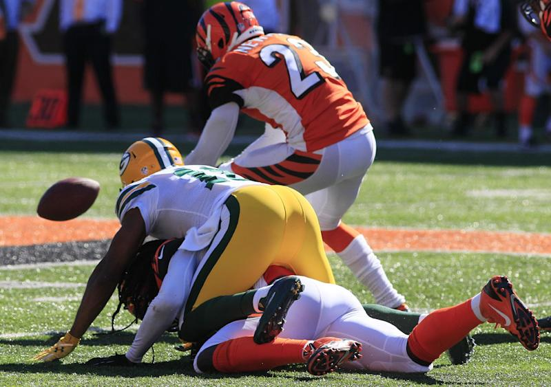 Cincinnati Bengals cornerback Terence Newman, top, recovers a fumble by Green Bay Packers tight end Andrew Quarless in the second half of an NFL football game, Sunday, Sept. 22, 2013, in Cincinnati. Newman returned the fumble 58 yards for a touchdown. (AP Photo/Tom Uhlman)