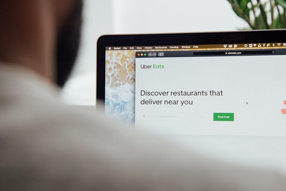 A man looks at the Uber Eats app on his laptop