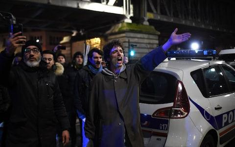 Protestors gesture next to a police car in front of the Bouffes du Nord theatre in Paris on January 17, 2020 as French President attends a play - Credit: LUCAS BARIOULET/AFP