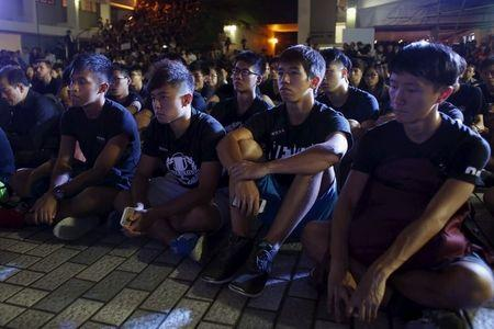 University students listen to a speech while wearing black at a rally at the University of Hong Kong in Hong Kong