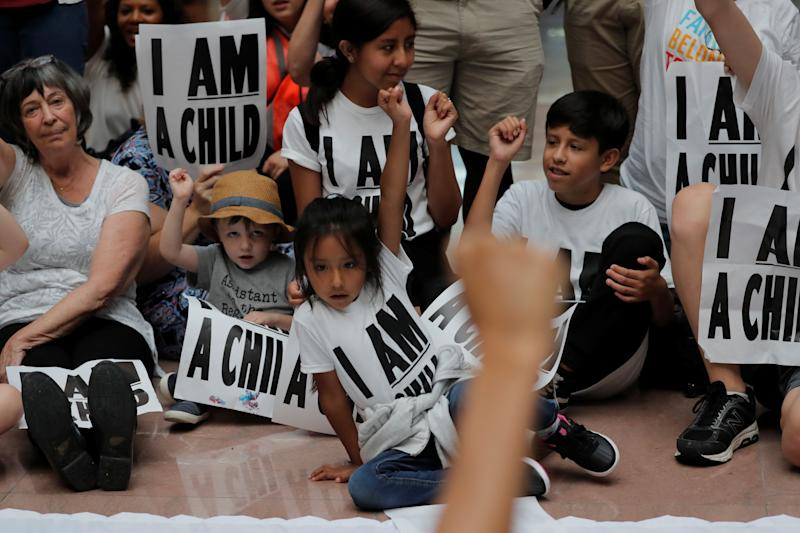 Children and parents sit in a Washington protest against Donald Trump's policy separating immigrant kids from their parents. (Reuters/Carlos Barria)