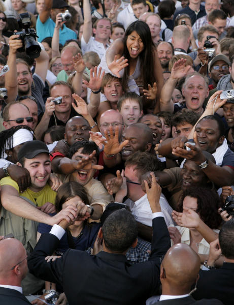 FILE - In this July 24, 2008 file photo, President-elect Barack Obama, bottom center, shakes hands with his supporters after speaking at the Victory Column in Berlin. In Europe, where more than 200,000 people thronged a Berlin rally in 2008 to hear Obama speak, there's disappointment that he hasn't kept his promise to close the military prison at Guantanamo Bay, and perceptions that he's shunting blame for the financial crisis across the Atlantic. (AP Photo/Jae C. Hong, File)