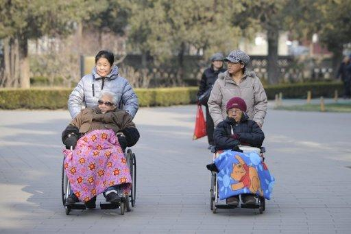 Two elderly people are seen on their wheelchairs at a park in Beijing, on December 11, 2012