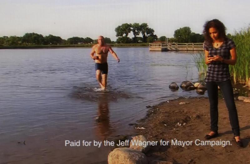 In this undated 2013 frame from a campaign ad video that went viral, Minneapolis mayoral candidate Jeff Wagner, an airport baggage handler, emerges from a local lake in a swimsuit. Wagner calls himself a regualr guy who is trying to wake people up. (AP Photo/Wagner Campaign)