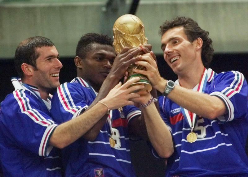FILE - In this Sunday, July 12, 1998 file photo, French teammates from left, Zinedine Zidane, Marcel Desailly and Laurent Blanc hold the soccer World Cup after France defeated Brazil 3-0 in the World Cup final soccer match, at the Stade de France in Saint Denis. (AP Photo/Michel Euler, File)