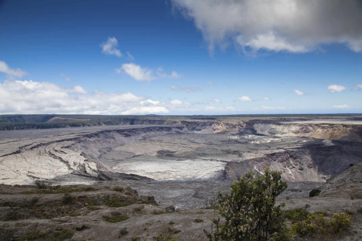 This photo provided by the National Park Service shows Halemaumau Crater, which has quadrupled in size since May, and Kilauea Caldera at Kilauea volcano's summit inside Hawaii Volcanoes National Park in Hawaii on Friday, Aug. 17, 2018. Slowing activity at Hawaii's Kilauea volcano is prompting scientists to downgrade their alert level for the mountain. (Janice Wei/National Park Service via AP)