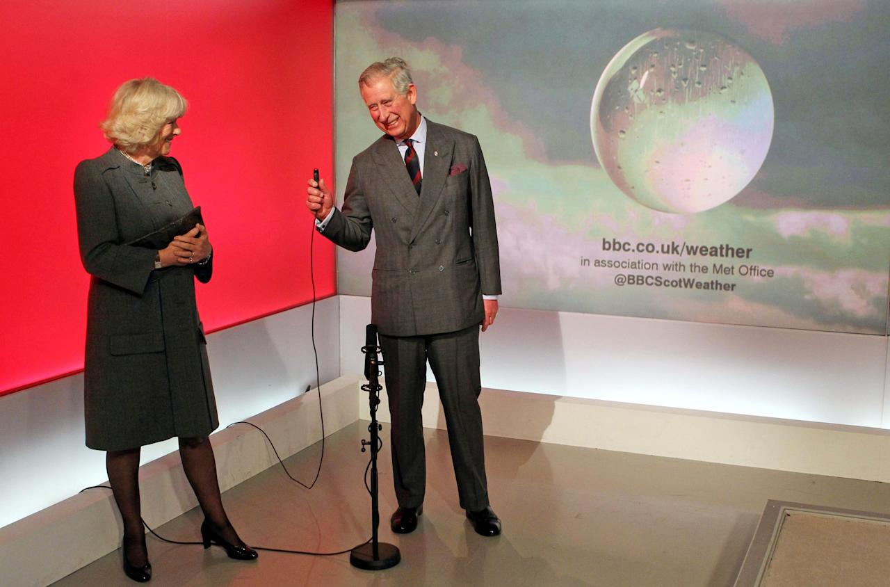 Britain's Prince Charles and Camilla the Duchess of Cornwall read the weather in the Six O'Clock studio whilst on a tour of the BBC Scotland Headquarters in Glasgow, Scotland where they met staff to celebrate sixty years of BBC Scotland Television Thursday May 10, 2012. (AP Photo/Andrew Milligan/PA Wire) UNITED KINGDOM OUT
