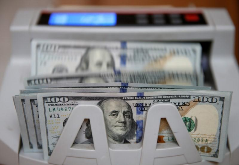 Money counter counts 100 U.S dollar banknotes in Kiev