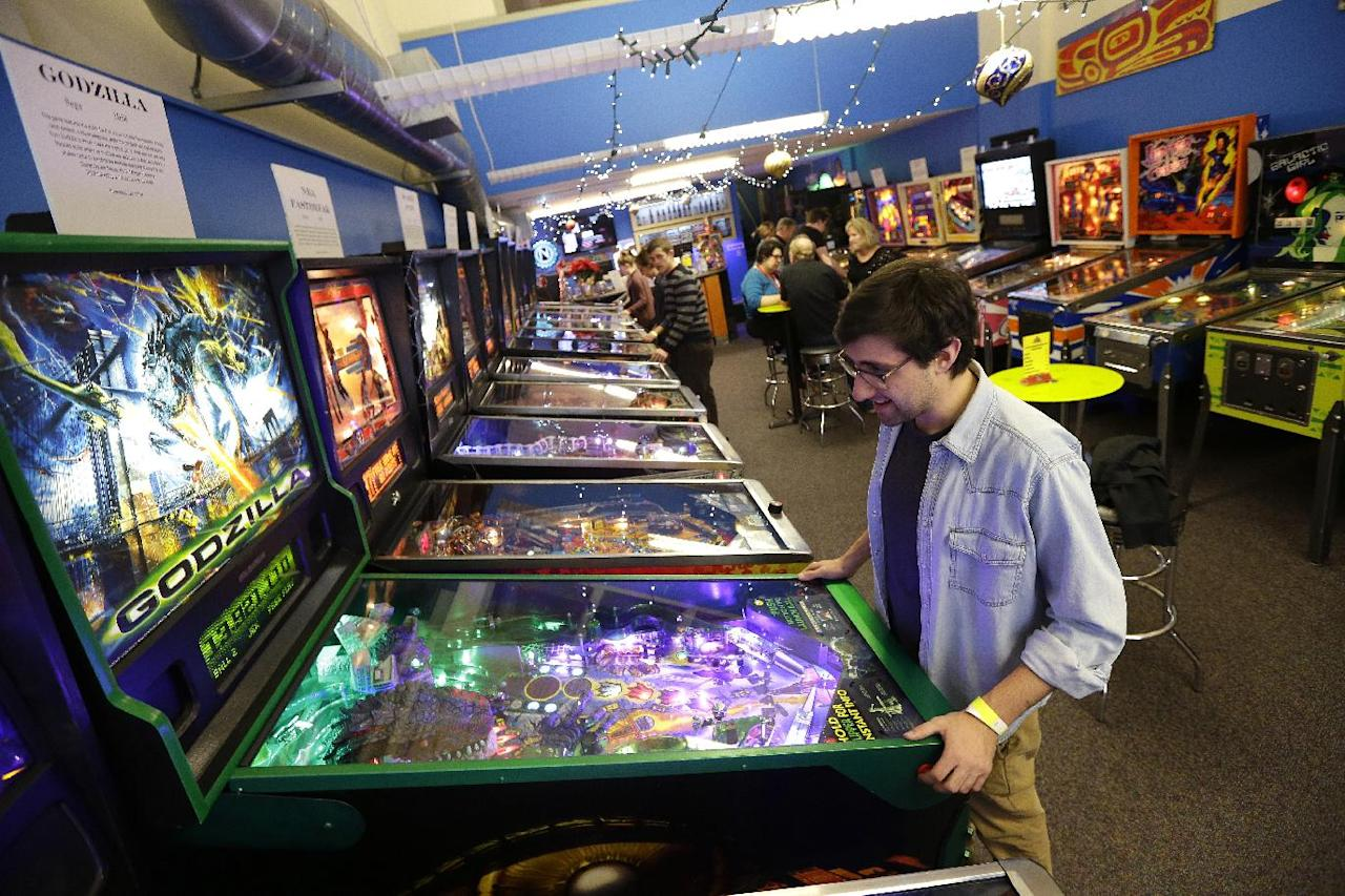 In this Dec. 16, 2013 photo, Josh Saitelbach plays pinball on an 1998 Godzilla machine as he visits the Seattle Pinball Museum in Seattle. The museum allows visitors who pay the admission fee to play unlimited rounds on the machines, which range from the 1960s to modern-day games. (AP Photo/Ted S. Warren)
