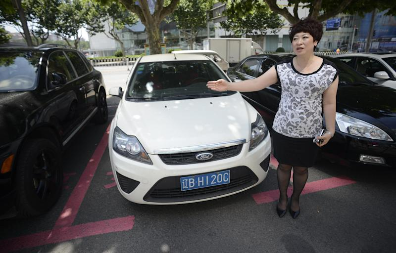 Mall manager Yang Hongjun speaks next to women-only parking spaces at the World Metropolis centre in Dalian on July 7, 2014 (AFP Photo/Johannes Eisele)