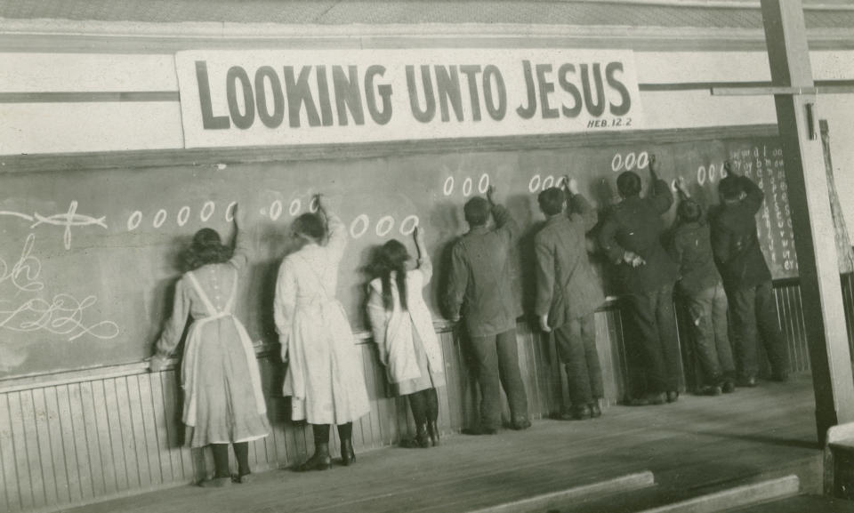 In this 1910s photo provided by the United Church of Canada Archives, students write on a chalkboard at the Red Deer Indian Industrial School in Alberta. In Canada, where more than 150,000 Indigenous children attended residential schools over more than a century, a National Truth and Reconciliation Commission identified 3,201 deaths amid poor conditions. (United Church of Canada Archives via AP)