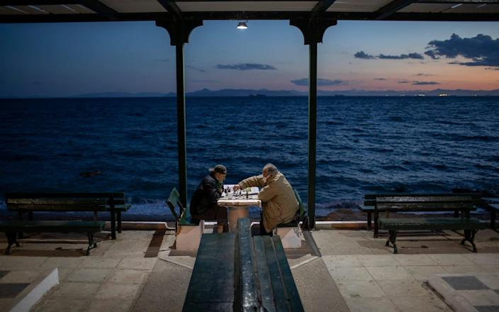 Two men wearing protective face masks play chess in Alimos, a seaside suburb of Athens - Petros Giannakouris/AP