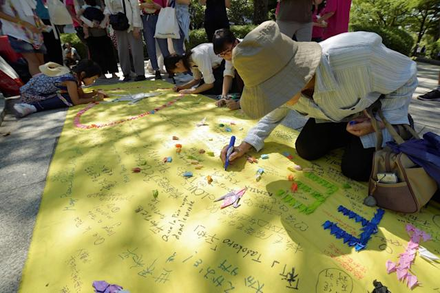 <p>People write down peace messages at Hiroshima Peace Memorial Park on Aug. 6, 2017 in Hiroshima, Japan. (Photo: David Mareuil/Anadolu Agency/Getty Images) </p>