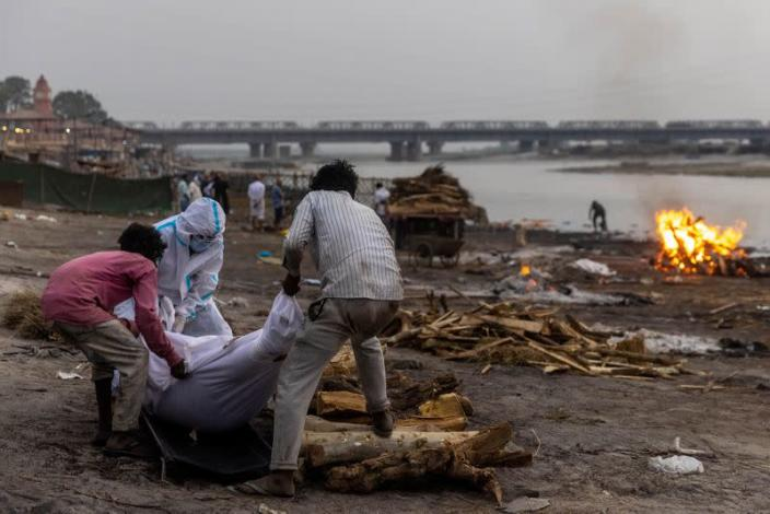 People place the body of a man who died from the coronavirus disease (COVID-19), on a pyre before his cremation on the banks of the river Ganges at Garhmukteshwar