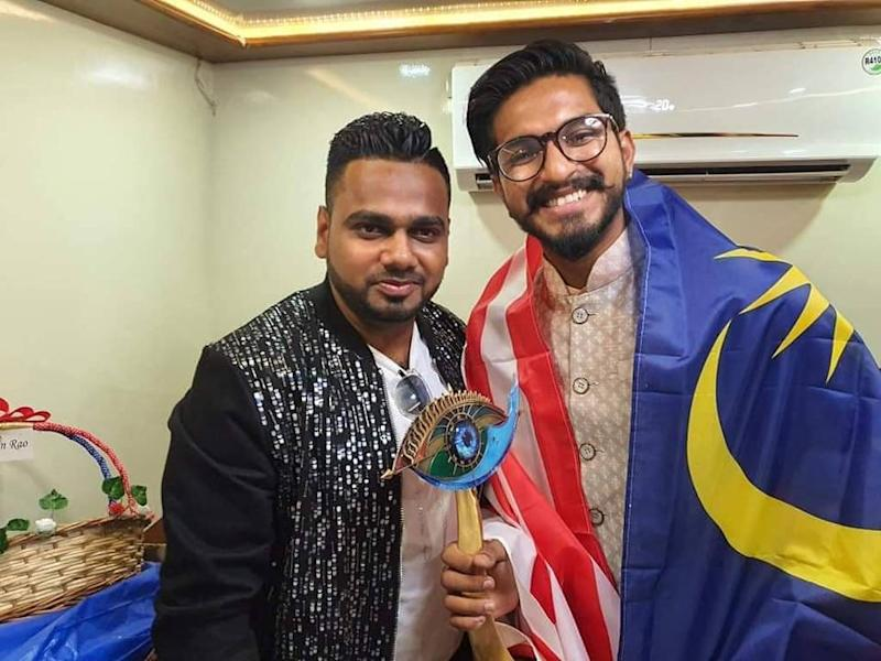 """Mugen Rao (R), a Jalur Gemilang (Malaysian flag) draped over his shoulders, proudly holding up his """"Bigg Boss"""" trophy."""