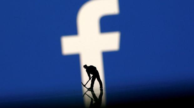 A figurine is seen in front of the Facebook logo