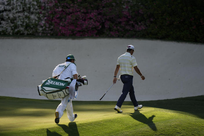 Hideki Matsuyama, of Japan, is followed by his caddie Shota Hayafuji as he walks off the 13th green during the final round of the Masters golf tournament on Sunday, April 11, 2021, in Augusta, Ga. (AP Photo/Matt Slocum)