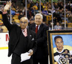 FILE - In this Jan. 19, 2008, file photo, former Boston Bruins hockey player Willie O'Ree waves to the crowd in Boston after being honored on the 50th anniversary of breaking the color barrier in the NHL after the first period of the Bruins hockey game against the New York Rangers in Boston. Looking on is Bruins legend John Bucyk. The Boston Bruins say they are retiring the jersey of Willie O'Ree, who broke the NHL's color barrier. O'Ree will have his jersey honored prior to the Bruins' Feb. 18 game against the New Jersey Devils. He became the league's first Black player when he suited up for Boston on Jan. 18, 1958 against the Montreal Canadiens, despite being legally blind in one eye.(AP Photo/Winslow Townson, File)