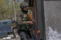 Indian army officers stand guard at the site of a shootout on the outskirts of Srinagar, Indian controlled Kashmir, Thursday, April 1, 2021. Gunmen in disputed Kashmir on Thursday killed a policeman as they tried to storm the residence of a politician of India's ruling party, police said. (AP Photo/ Dar Yasin)