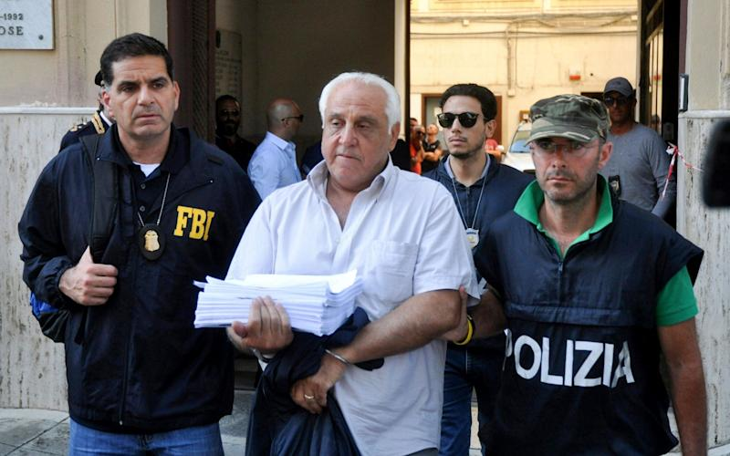 An FBI officer and an Italian police officer escort a suspect named Tommaso Inzerillo after he was arrested in Palermo during a joint operation called 'New Connection' - AFP