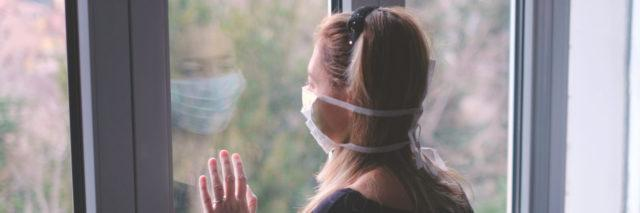 Woman wearing a mask looking out the window during the coronavirus pandemic.