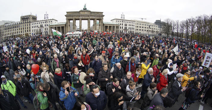 FILE - In this Wednesday, Nov. 18, 2020 file photo, people attend a protest rally in front of the Brandenburg Gate in Berlin, Germany against the coronavirus restrictions in Germany. Nations are struggling to reconcile cold medical advice with a holiday tradition that calls for big gatherings in often poorly ventilated rooms, where people chat, shout and sing together, providing an ideal conduit for a virus that has killed over 350,000 people in Europe so far. (AP Photo/Michael Sohn, File)