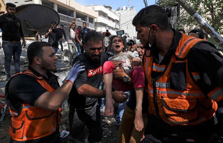 OPSHOT - Palestinian paramedics evacuate a girl from the rubble of a destroyed building in Gaza City's Rimal residential district on May 16, 2021, following massive Israeli bombardment on the Hamas-controlled enclave. - Israel's army said it had bombed the home of the political leader of Islamist group Hamas in the Gaza Strip, as the UN Security Council was to meet amid global alarm about the escalating conflict. (Photo by MAHMUD HAMS / AFP)