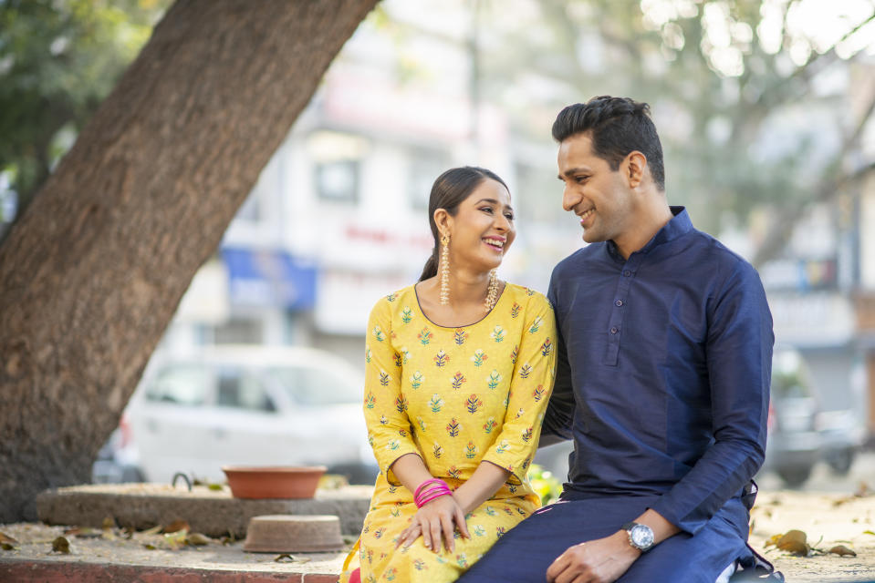 An Indian couple sits side by side while looking at each other lovingly. They are incredibly happy.