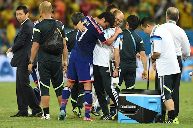 Japan's midfielder and captain Makoto Hasebe (C) hugs a coach after losing their Group C football match between against Colombia at the Pantanal Arena in Cuiaba during the 2014 FIFA World Cup on June 24, 2014 (AFP Photo/Toshifumi Kitamura)