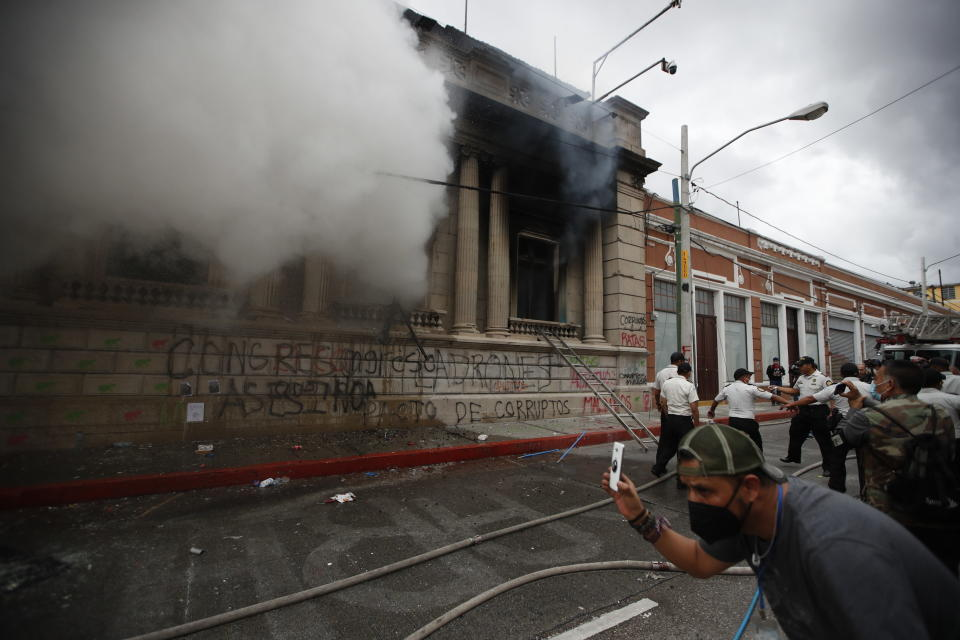 Clouds of smoke shoot out from the Congress building after protesters set a part of it on fire, in Guatemala City, Saturday, Nov. 21, 2020. Hundreds of protesters were protesting in various parts of the country Saturday against Guatemalan President Alejandro Giammattei and members of Congress for the approval of the 2021 budget that reduced funds for education, health and the fight for human rights. (AP Photo/Moises Castillo)