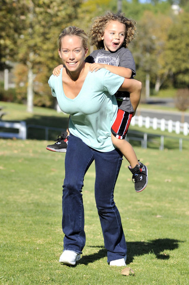 EXCLUSIVE: Kendra Wilkinson, her husband Hank and son Hank Jr. enjoy a sunny day in a local park over the Thanksgiving weekend. Kendra wipes out on the slide with her son before showing him the monkey bars. At one point Hank Jr. is driven around in a toy Cadillac by a young lady friend.