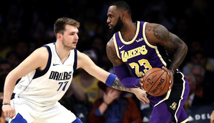 Los Angeles Lakers' LeBron James (23) is defended by Dallas Mavericks' Luka Doncic (77).