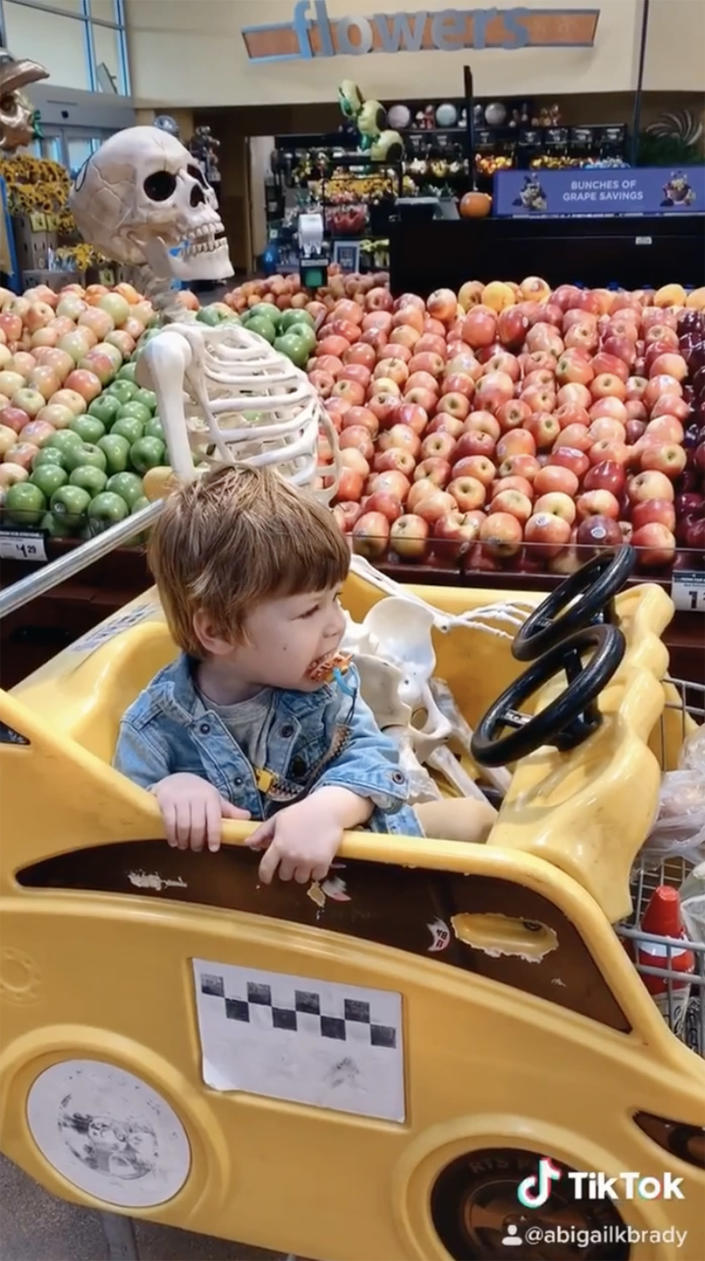Theo and Benny the skeleton ride together in grocery cart. (abigailkbrady / Instagram)