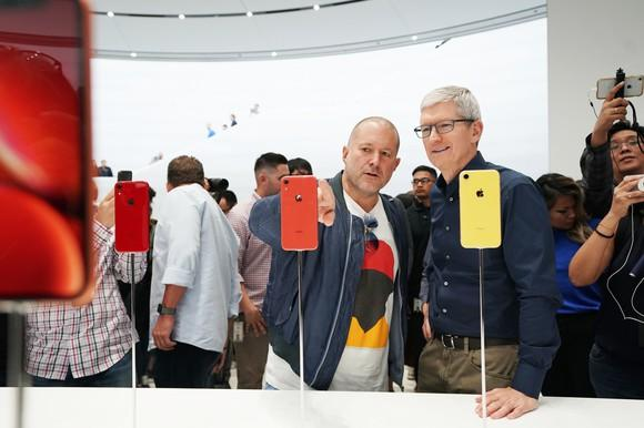 Apple executives Jony Ive and Tim Cook at a table with iPhone XR phones.