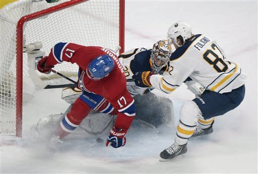Montreal Canadiens' Rene Bourque slides in on Buffalo Sabres' goaltender Ryan Miller, centerre, and Marcus Foligno (82) during first period NHL hockey action in Montreal, Saturday, Feb. 2, 2013. (AP Photo/The Canadian Press, Graham Hughes)