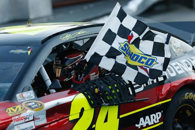 Jeff Gordon (24) holds the checkered flag as he celebrates winning the NASCAR Sprint Cup auto race at Martinsville Speedway Sunday, Oct. 27, 2013, in Martinsville, Va. (AP Photo/POOL,Geoff Burke)