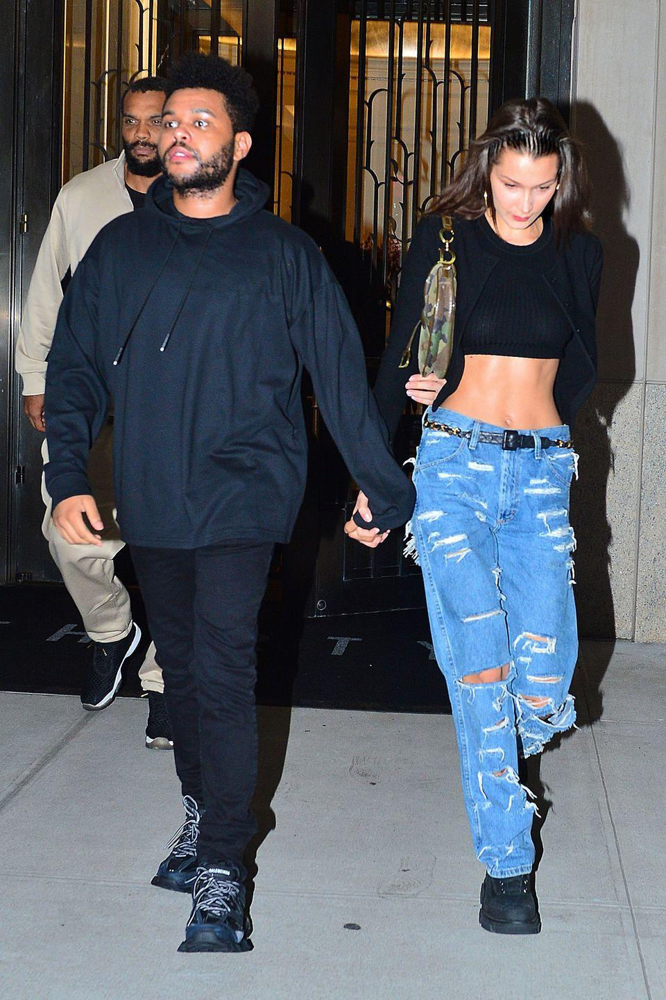 """<p>In a black crop top and jacket, low rise ripped jeans, black hiking boots and a camouflage <a href=""""https://www.dior.com/couture/en_us/womens-fashion/saddle-bags"""" rel=""""nofollow noopener"""" target=""""_blank"""" data-ylk=""""slk:Dior saddle bag"""" class=""""link rapid-noclick-resp"""">Dior saddle bag</a> out in NYC with The Weeknd.</p>"""