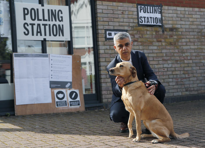 Mayor of London Sadiq Khan holds his dog Luna as his wife Saadiya votes at St Albans Church in London, Thursday, May 6, 2021. Khan voted by post. Millions of people across Britain will cast a ballot on Thursday, in local elections, the biggest set of votes since the 2019 general election. A Westminster special-election is also taking place in Hartlepool, England. (AP Photo/Frank Augstein)