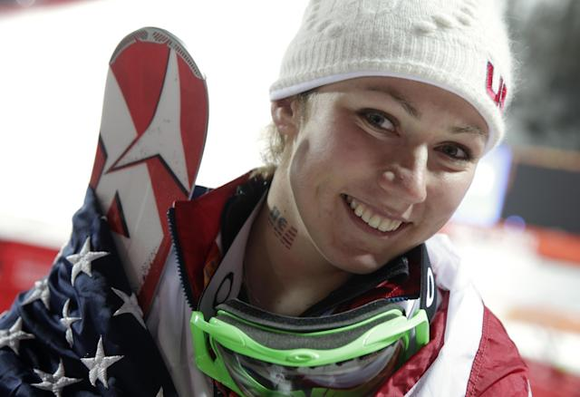 Women's slalom gold medal winner Mikaela Shiffrin of the United States wears an American flag after a flower ceremony at the Sochi 2014 Winter Olympics, Friday, Feb. 21, 2014, in Krasnaya Polyana, Russia.(AP Photo/Gero Breloer)