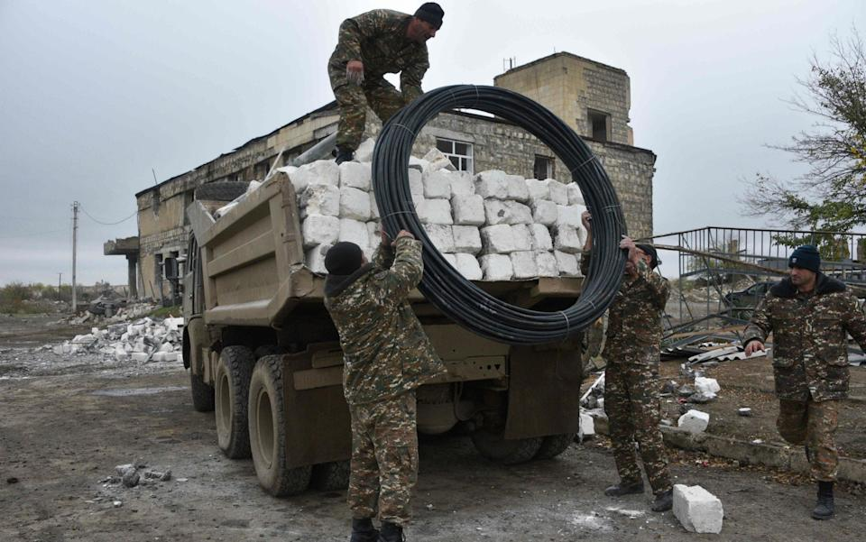 Armenian soldiers evacuate their headquarters from the town of Agdam - AFP