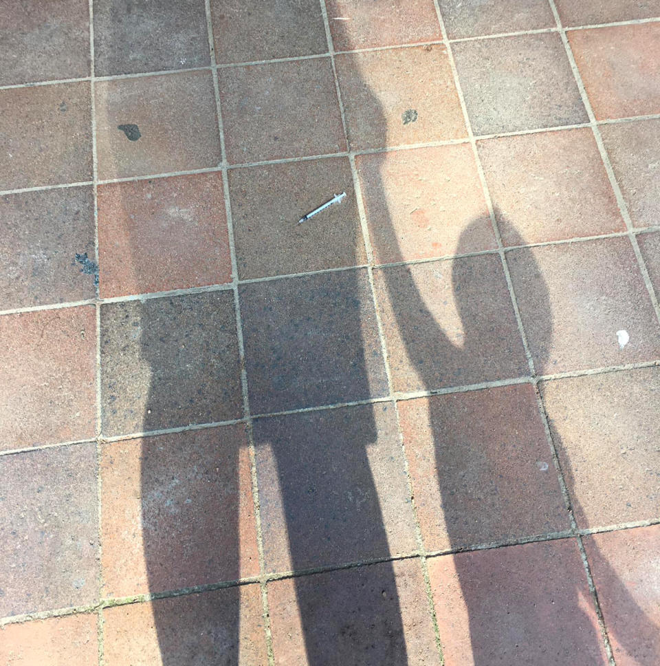 A needle lies on the pavement in front of the shadow of a mum and her child.