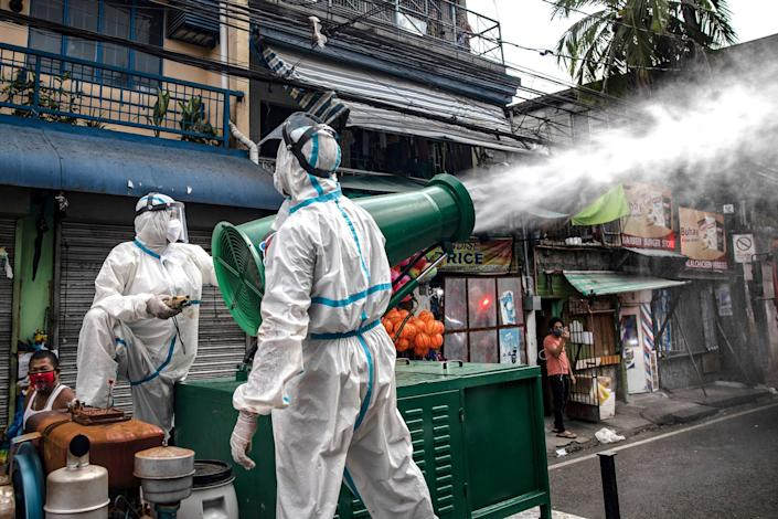 Disinfection workers spray disinfectant from a water cannon along a street at a suburban area on March 23, 2020 in San Juan, Metro Manila, Philippines.