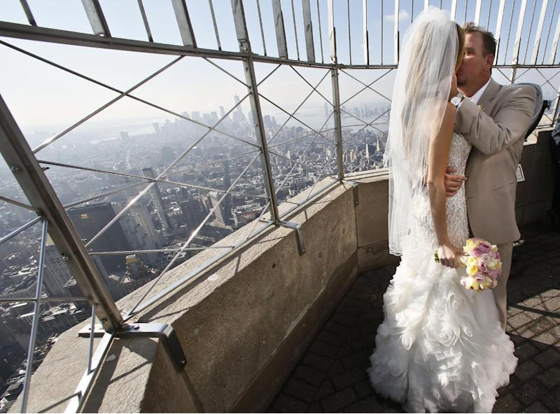 """Newlyweds Danielle Brabham, 39, and Michael Lynch, 41, from Miami Shores, Fla., kiss while posing for pictures on the Empire State Building viewing platform after their Valentine's Day wedding on Thursday, Feb. 14, 2013 in New York. Brabham and Lynch were among three couples chosen for the 19th Annual Weddings Event, """"Love is in the Air,"""" designed by celebrity designer Preston Bailey, after submitting their personal love stories to the Empire State Building's Facebook page. (AP Photo/Bebeto Matthews)"""