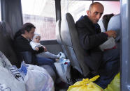People sit in a bus as they prepare to leave Stepanakert, the separatist region of Nagorno-Karabakh, Friday, Oct. 30, 2020. The Azerbaijani army has closed in on a key town in the separatist territory of Nagorno-Karabakh following more than a month of intense fighting. (AP Photo)