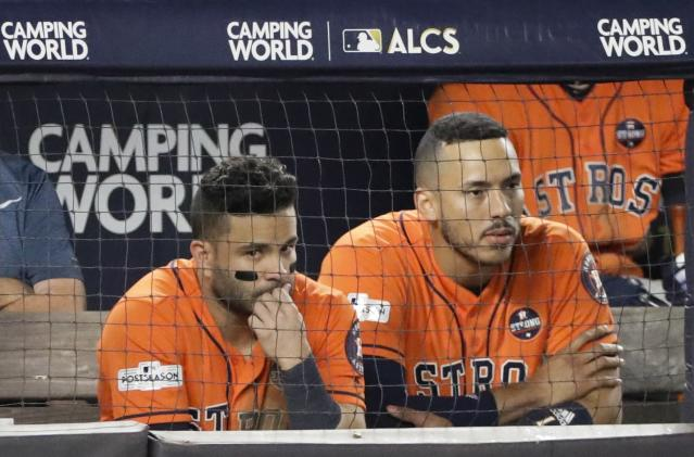 Houston Astros' Jose Altuve and Carlos Correa watch from the dugout during the seventh inning of Game 5 of baseball's American League Championship Series against the New York Yankees Wednesday, Oct. 18, 2017, in New York. (AP Photo/David J. Phillip)