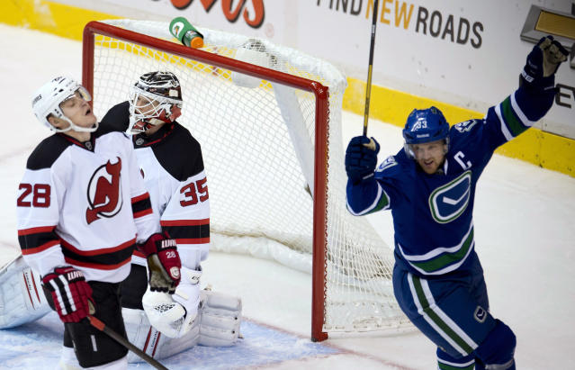 Vancouver Canucks center Henrik Sedin, right, celebrates teammate Daniel Sedin's goal past New Jersey Devils goalie Cory Schneider (35) as Devils defenseman Anton Volchenkov (28) skates past Schneider during the second period of an NHL hockey game Tuesday, Oct. 8, 2013, in Vancouver, British Columbia. (AP Photo/The Canadian Press, Jonathan Hayward)