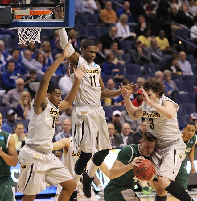 Cal Poly forward Zach Gordon is surrounded by Wichita State defenders Darius Carter (left), Cleanthony Early (11) and Evan Wessel, RIGHT, during the first half of a second-round game in the NCAA college basketball tournament Friday, March 21, 2014, in St. Louis. (AP Photo/St. Louis Post-Dispatch, Chris Lee)