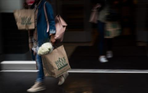 A customer carries shopping bags outside a Whole Foods Market location in New York. It has been facing pressure from restless shareholders after nearly two years of sliding sales.
